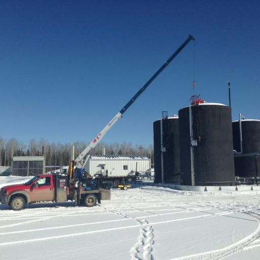 Red truck with a crane in snowy oilfield